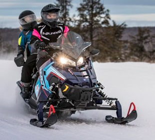 Two people riding on a blue Polaris snowmobile